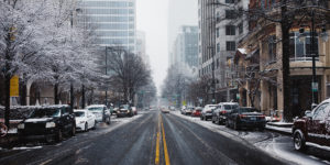 photo of a snowy urban street with trees, parked cars, and buildings