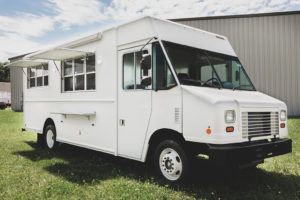 photo of a white food truck parked in grass in front of a warehouse