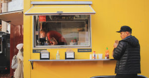 patrons getting food from a yellow food trailer