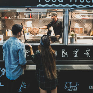 man and woman buying food from a food truck