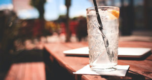 glass of ice water on a picnic table in the sun
