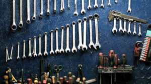 wrenches and other tools hanging on a work bench